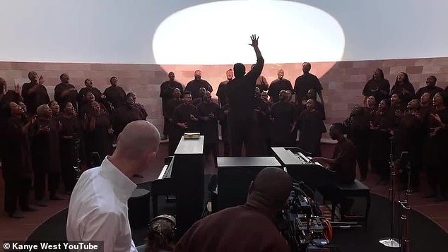 Holy moment:We then move to one of the interior spaces of the installation, known as the Crater's Eye, with West filming his choir as they sing spiritedly and in unison