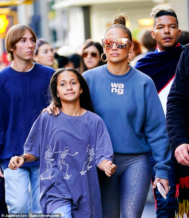 The look: JLo insulated herself on the cool Fall day in a blue sweater bearing the letters 'wang' across the front