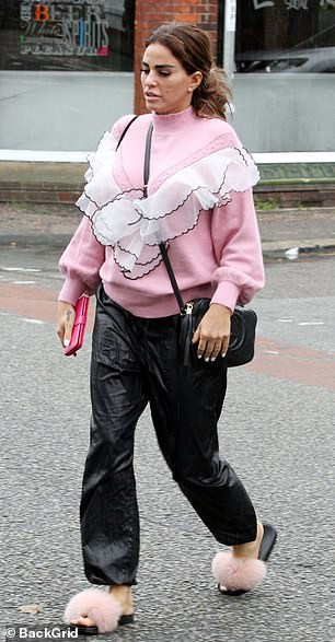 Signature style: Katie was casually-clad for the low-key trip, donning a cosy pink jumper with ruffle detailing