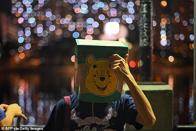 A protester covers his face with a paper bag displaying a Winnie the Pooh image as he takes part in the human chain rally in Sha Tin district in Hong Kong on Friday. PewDiePie showed a series of memes featuring Chinese President Xi and the cartoon bear to support Hong Kong