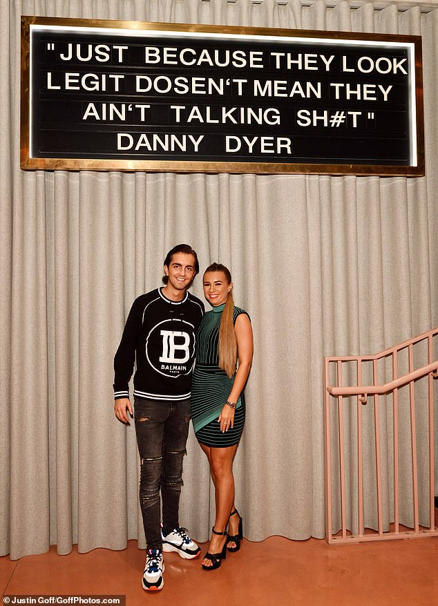 Naughty: The happy couple posed beneath a sign displaying a quote from her father Danny, which read: 'Just because they look legit doesn't mean they ain't talking s***'