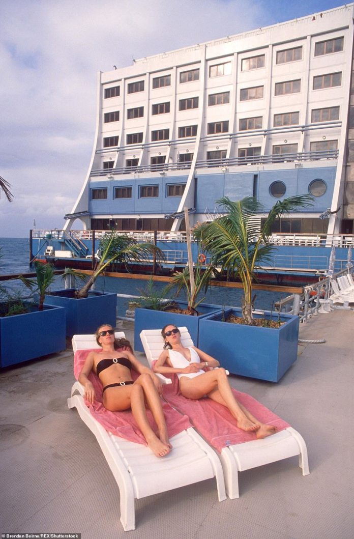 A pair of guests relax on sun loungers at the hotel in 1988 before it was moved thousands of miles away to Vietnam