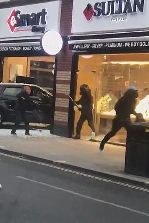 As onlookers attempt to approach a man inside the shop, an apparent thief in a motorcycle helmet rushes out of the Sultan Jewellers, which is joined internally to the shop they raided