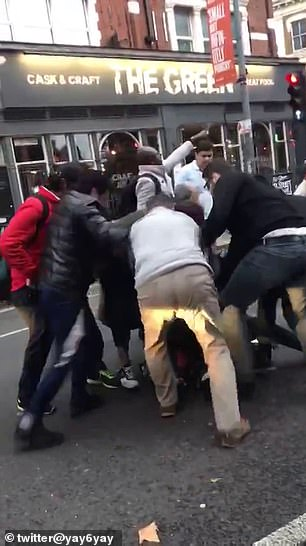 Pedestrians rush to the thief, who had dropped a bag on the ground when he fell, and attempt to restrain him while other onlookers film the scenes