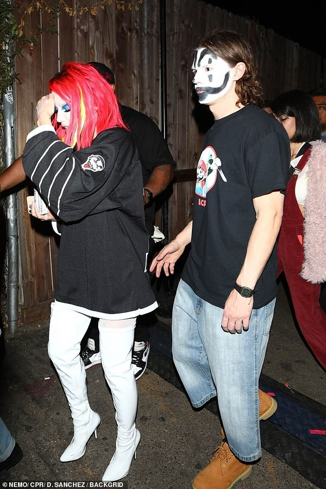 Out and about: Donning an edgy red wig, the singer wore full white facepaint and sexy thigh-high boots while Evan wore a similar style mask