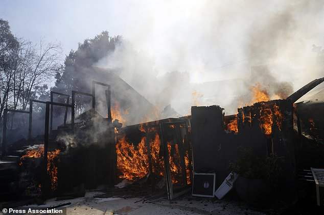 Up in flames: A wildfire-ravaged home burns as crews continue to battle the Getty fire