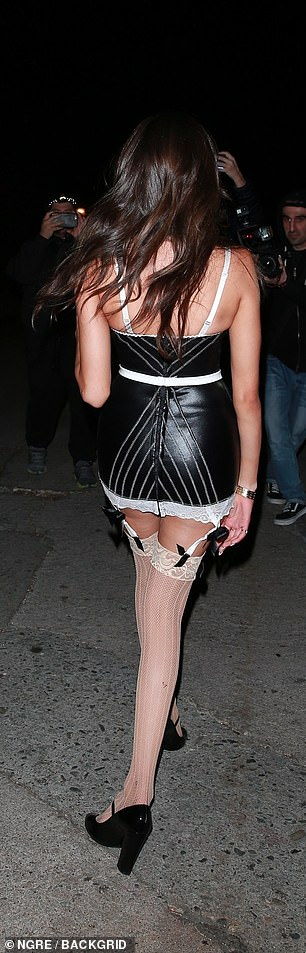 Sexy: She wore white suspended stockings attached by garters and decorated the look with black satin bows