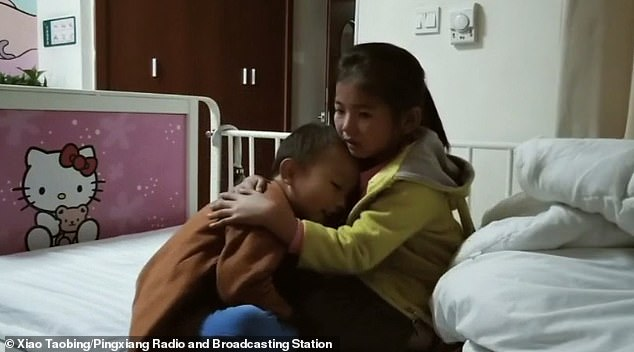 The six-year-old loving sister then cuddles her four-year-old brother in his hospital ward
