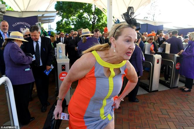 Determination: One woman in a red and grey dress was resolutely focused on running to the stands ahead of the race