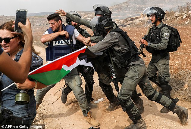On Sunday, the Palestinian Liberation Organization slammed Israel over the incident and urged the United Nations to act. Pictured: Scuffles betweenIsraeli border guards and a photojournalist