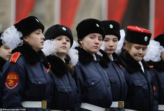 Five women cadets dressed in hats and military jackets watch the dress rehearsal taking place in Moscow, Russia today