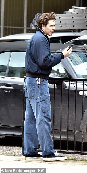 Off to 'work': He slung a navy jacket with a plaid trim over his torso and looked unshaven and bed-headed as he chatted on his phone while walking to the studio