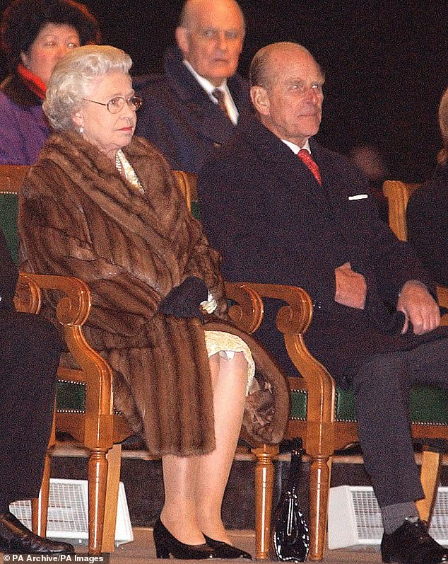The Queen enjoys a performance in Winnipeg, Canada, wearing the brown fur coat in 2002