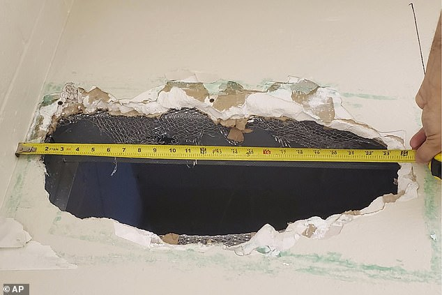 The pair had created a hole measuring eight inches tall and 22 inches wide (pictured) in the guards' blind spot and then slipped into the walls of the jail, authorities said