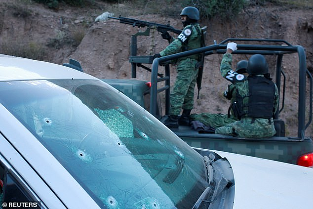 Soldiers assigned to Mexico's National Guard pass by a bullet-riddled vehicle belonging to one Mexican-American Mormon family caught up in the slaughter on Monday