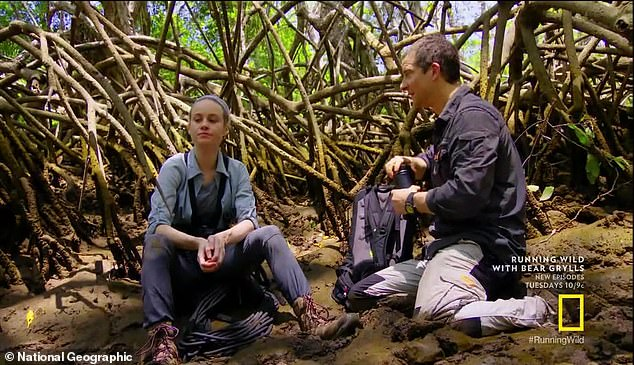 Break: They sit down and Bear teaches Brie a survival tip, saying it's 'mosquito central' and he tells her to cover herself in mud