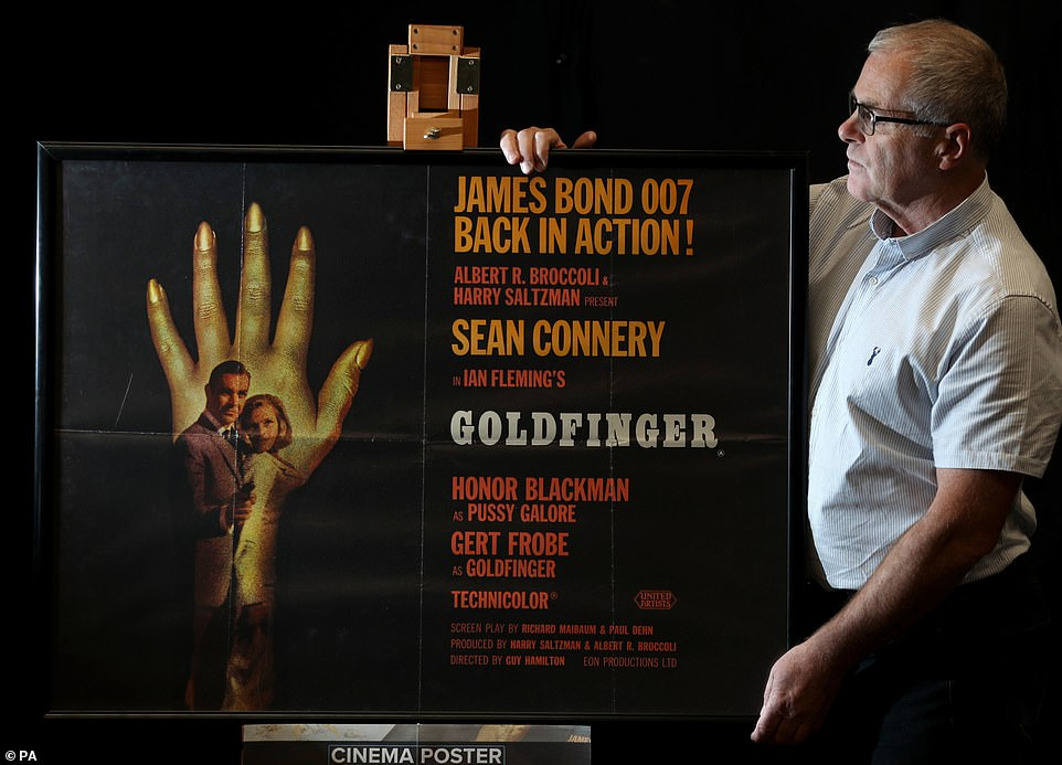 The sale attracted global interest. Pictured: Prop Store poster consultant Mike Bloomfield adjusts a Style-B Quad Poster for the 1964 James Bond film Goldfinger that had an estimate of £5,000-£7,000