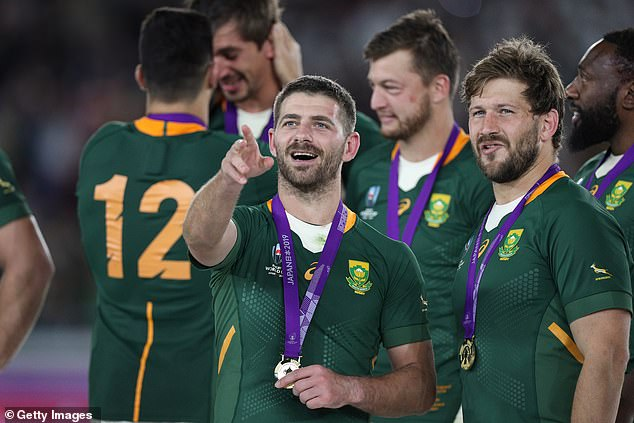 Willie le Roux and Frans Steyn toast to their success with their medals during the ceremony