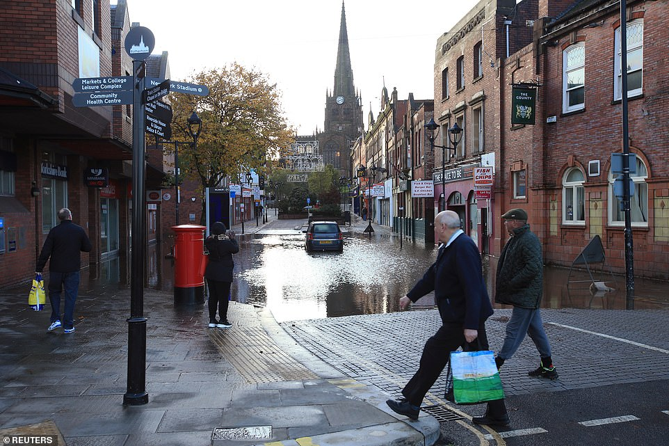 People walk past a car in floodwater in Rotherham today as South Yorkshire is hit by heavy rainfall and flooding