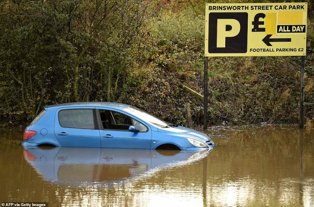 An abandoned car is pictured in a flooded car park in Rotherham, South Yorkshire, this morning