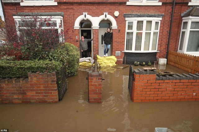Residents in Yarborough Terrace in Doncaster look at the floodwater today following a deluge of rain in South Yorkshire
