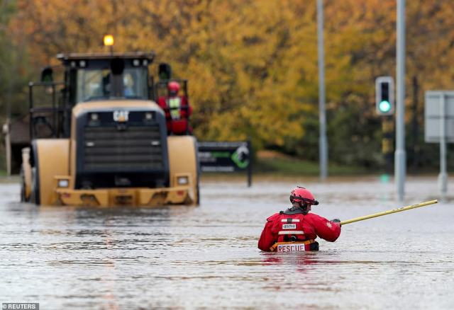 An emergency service worker stands on a flooded road in Rotherham today as he tries to help people in need of assistance