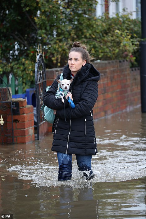 A woman carries her dog through floodwater in Doncaster