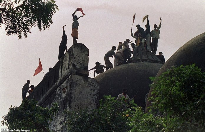 Hindu fundamentalists scream and wave banners at the top of a stone wall and celebrate the destruction of the sixteenth century Babri Mosque in Ayodhya on December 7, 1992.