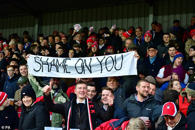 The Gloucester supporters hold up a banner saying 'SHAME ON YOU' directed at Saracens