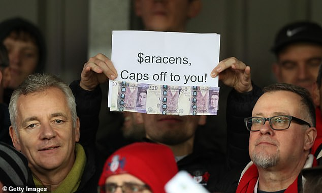 One fan holds up a piece of paper saying '$aracens, Caps off to you!' with £20 notes attached