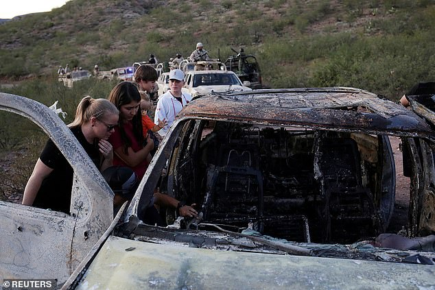 Family members and friends watch the burned remains of Rhonita Miller LeBaron's Tahoe SUV after the fire that took place during the massacre (photo).