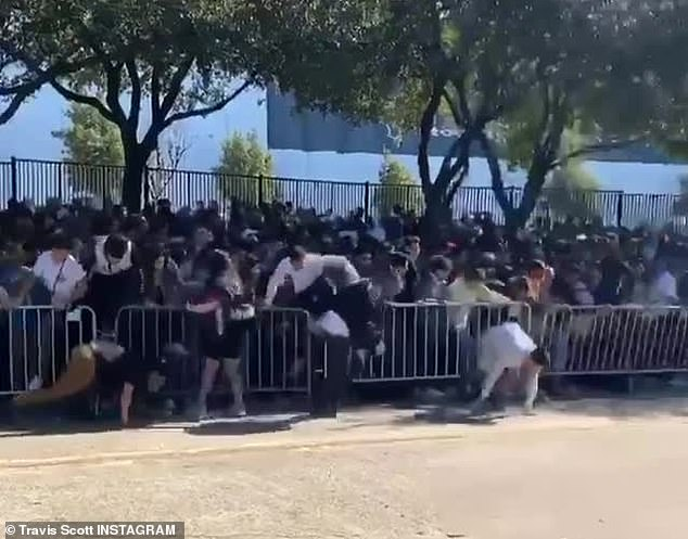 Stampede! A video posted to Scott's Instagram shows several attendees jumping over barricades before knocking them over altogether