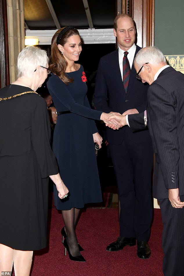 Opting for a boat neck navy dress with three poppies, Kate cut an elegant figure as she arrived in West London for the Royal British Legion Festival of Remembrance