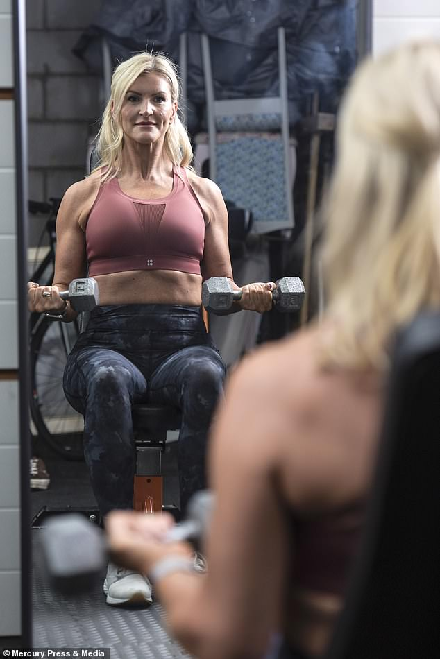 The mother (pictured at the gym) undergoes strength workouts including shoulder presses and sled drags