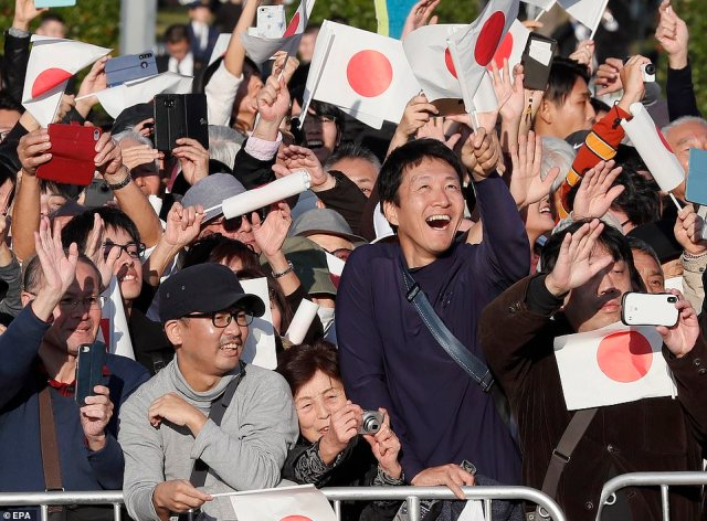 Well-wishers enthusiastically wave their national flag as they celebrate the new Emperor of Japan, who was proclaimed the role on October 22