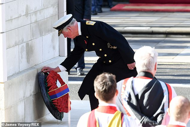 The Prince of Wales laid the first wreath on behalf of the Queen, who watched the service from a nearby balcony