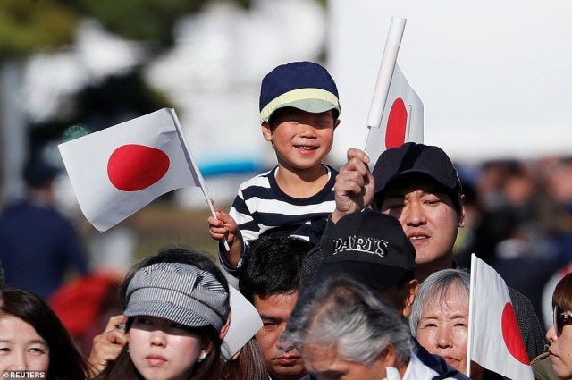 A little boy, who is sat on someone's shoulder, is pictured with a wide smile across his face. The parade was the first since Naruhito and Masako's marriage in June 1993, just three years after their parents celebrated their enthronement in a Rolls Royce