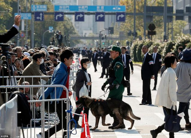 A police dog stands on guard along the three-mile strip of the parade to keep an eye on the excited well-wishers. Some camped overnight to get a good spot in full view of the Emperor