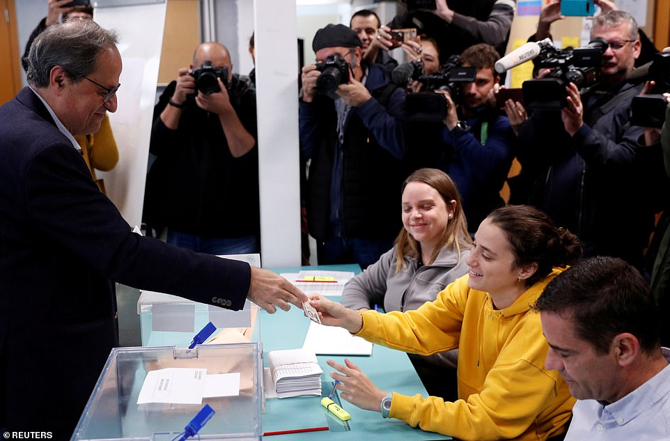 In Barcelona, Spain's Catalan leader Quim Torra casts his vote as daughter Helena Torra, wearing yellow, works at the polling station. This election has been marred by heightened tensions over Catalonian independence and a surge in support for Vox