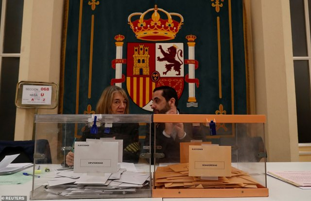 Two election workers watch as votes are cast in the country's capital Madrid. Polls close at 8pm, or 9pm tonight, with results expected a few hours after they close