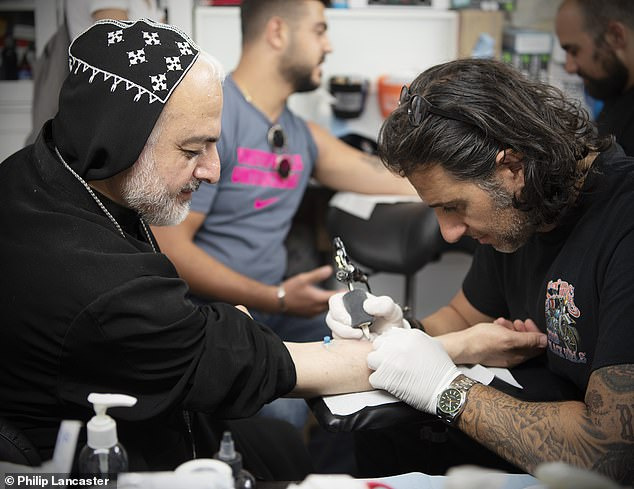Inking-man's tattoo parlour: Wassim Razzouk tattoos a Syriac Orthodox priest