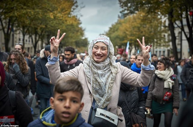 Protesters demonstrate as thousands took to the streets of Paris in the Anti-Islamophobia Rally on Sunday. One woman holds up her fingers and smiles