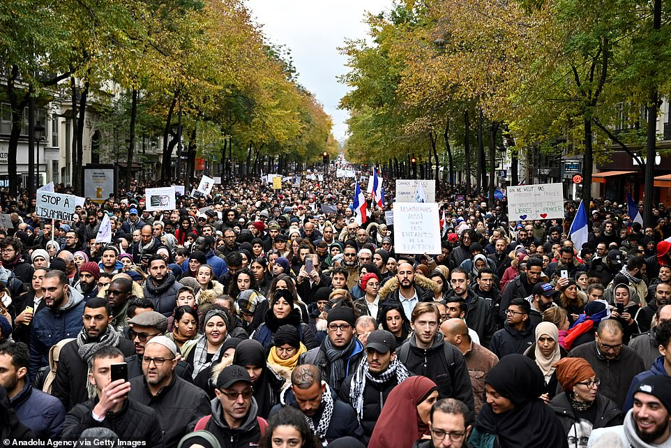 People hold placards during the demonstration to protest against Islamophobia, near the Gare du Nord in Paris, today