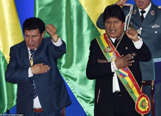 Pictured are Bolivia's president of the lower house of parliament Victor Borda and now former President Evo Morales as they sing the national anthem during the celebration of the 194th anniversary of the country's Independence. Morales, first elected in 2006, was seeking to remain in power until 2025 after he took legal action to get around constitutional term limits
