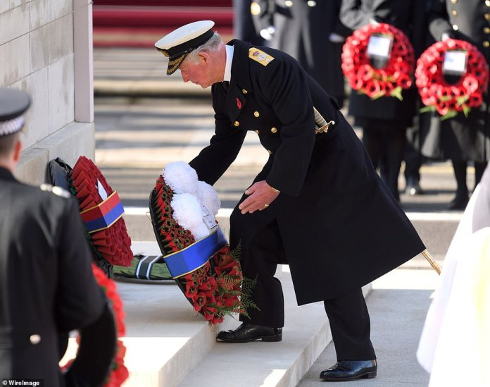 Prince Charles is pictured above with a wreath. The Queen, flanked by the Duchesses of Cornwall and Cambridge, watched from a balcony as the Prince of Wales placed her wreath on the cenotaph before taking his own tribute
