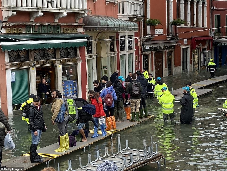 People wearing colourful waterproof overshoes stand on a temporary walkway amid fresh flooding in Venice this morning