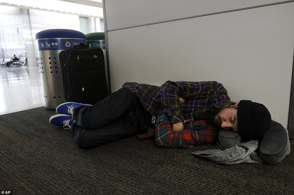 Ezra Allen sleeps while waiting to board a flight to Tampa Bay at San Francisco International Airport in San Francisco, Tuesday, Northern California and southern Oregon residents are bracing for a 'bomb cyclone' that's expected at one of the busiest travel times of the year. The storm had already closed highways across the region and canceled and delayed hundreds of flights in and out of Denver on Tuesday