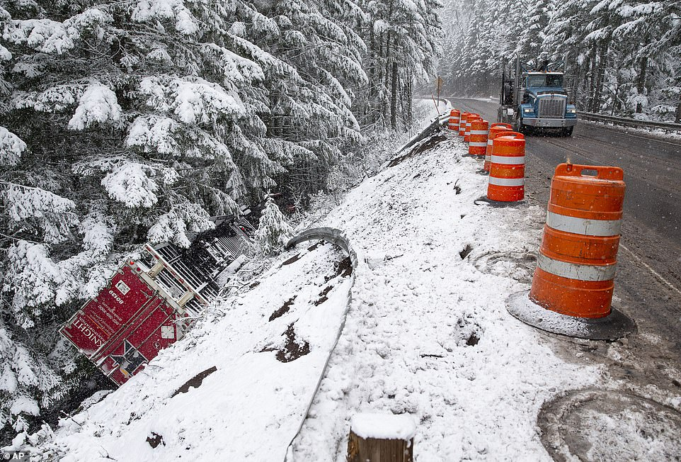 A tractor trailer rests upside down after it left Highway 58, east of Oakridge, Oregon, under snowy conditions Monday