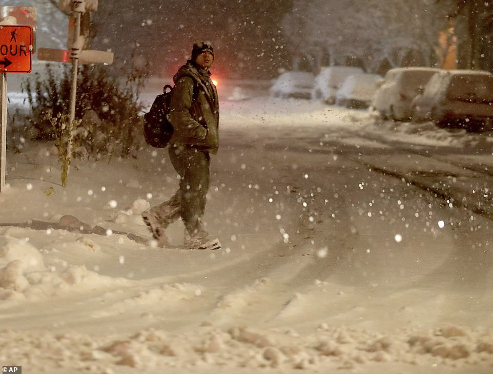A pedestrian walks in downtown Minneapolis, Wednesday. Blinding snow is falling fast in southern Minnesota