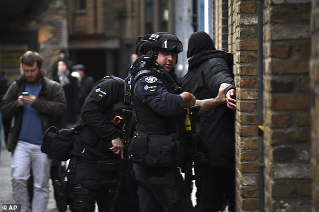 Police apprehend a man in an street on the south side of London Bridge today as they respond to the incident. Other members of the public seem to be walking past obliviously